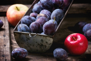Vintage metal bowl with plums and apples over old wooden table. See sries
