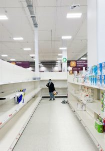 woman looking at an empty grocery store aisle