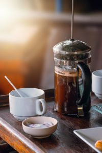 French press coffee maker and cup